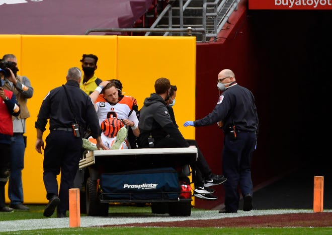 Nov 22, 2020; Landover, Maryland, USA; Cincinnati Bengals quarterback Joe Burrow (9) leaves the field after suffering an apparent  knee injury during the second half against the Washington Football Team at FedExField.