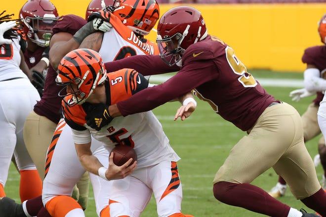 Washington Football Team defensive end Montez Sweat (90) sacks Cincinnati Bengals quarterback Ryan Finley (5) in the third quarter at FedExField on Sunday.