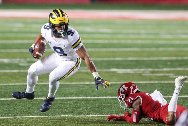 Michigan Wolverines running back Chris Evans (9) carries the ball against Rutgers Scarlet Knights defensive back Tre Avery (21) during the first half at SHI Stadium.