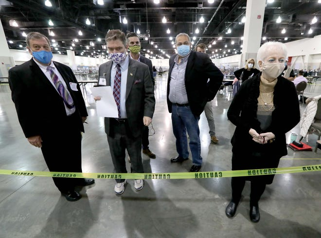 Officials stand behind tape near voting machines where the Trump campaign felt were too far from observers to see what was happening at the presidential election recount at the Wisconsin Center in Milwaukee on Sunday.  Pictured are from left to right, Stuart Karge, an attorney for President Donald Trump, Milwaukee County Clerk, George Christenson Election Commissioners, Tim Posnanski Rick Baas, and Dawn Martin.
