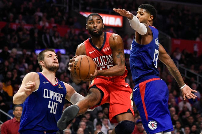 New Orleans Pelicans guard E'Twaun Moore, center, moves the ball past Los Angeles Clippers forward Paul George, right, during the second half of an NBA basketball game in Los Angeles, Sunday, Nov. 24, 2019. The Clippers won 134-109. (AP Photo/Kelvin Kuo)