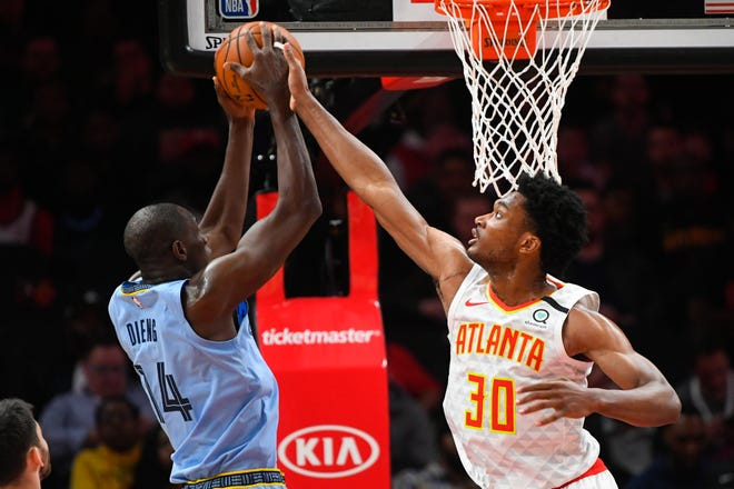 Atlanta Hawks center Damian Jones (30) defends against a shot by Memphis Grizzlies center Gorgui Dieng during the first half of an NBA basketball game Monday, March 2, 2020, in Atlanta. (AP Photo/John Amis).