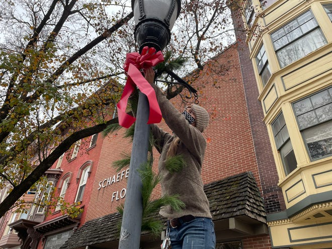 Volunteer Jamie Kinsley, a member of the York College Young Alumni Council, secures a garland and bow to a lamp post on Market Street.