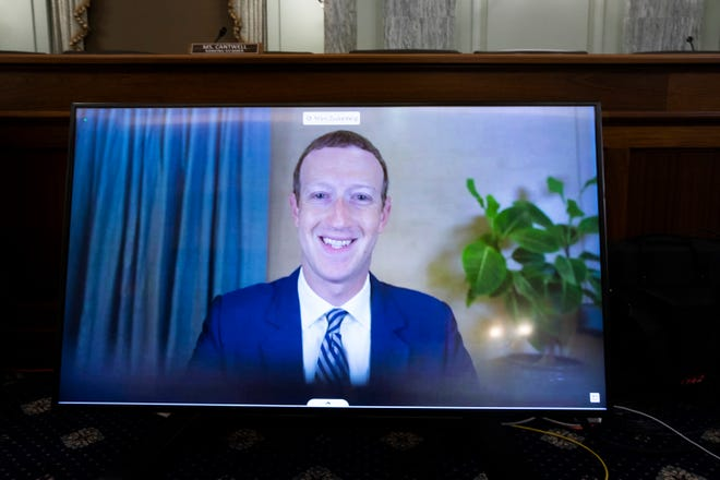"""CEO of Facebook Mark Zuckerberg appears on a monitor as he testifies remotely during the Senate Commerce, Science, and Transportation Committee hearing """"Does Section 230's Sweeping Immunity Enable Big Tech Bad Behavior?"""" on Oct. 28, 2020 on Capitol Hill in Washington, D.C. (Michael Reynolds/Pool/Getty Images/TNS)"""