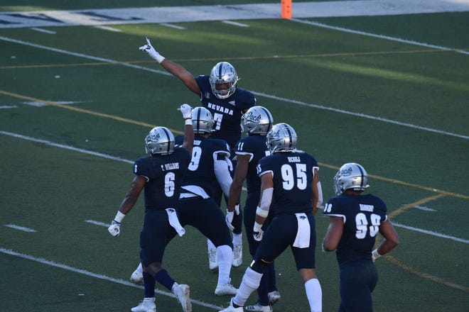 Nevada players celebrate a big play during the Wolf Pack's 26-20 win Saturday, Nov. 21, 2020, over visiting San Diego State at Mackey Stadium in Reno, Nev.