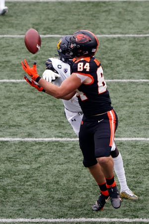 Nov 21, 2020; Corvallis, Oregon, USA; Oregon State Beavers tight end Teagan Quitoriano (84) catches a pass while being defended by California Golden Bears linebacker Kuony Deng (8) during the first half at Reser Stadium. Mandatory Credit: Soobum Im-USA TODAY Sports