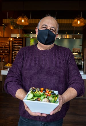 Shahin Movahedi, holds a vegetarian dish filled with various vegetables inside the Saffron Cafe in Monterey, Calif., on Friday, Nov. 20, 2020.