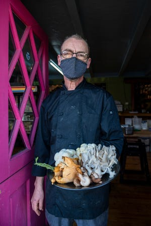 Neil Dunn, holds a plate full of fresh ingredients that they use for their vegetarian dishes inside Julia's Vegetarian Restaurant in Pacific Grove, Calif., on Friday, Nov. 20, 2020.