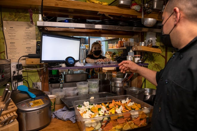 Jennifer Barnes, left, talks with Leo Razo inside Julia's Vegetarian Restaurant in Pacific Grove, Calif., on Friday, Nov. 20, 2020.
