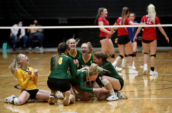 Members of the Northwestern volleyball team celebrate after winning the Class B state championship Saturday night in Huron.