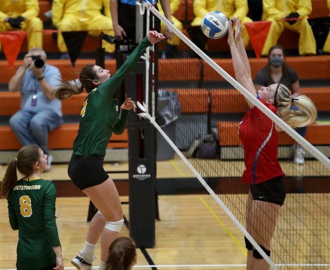 Northwestern's Hannah Schentzel, left, tries to hit the ball past Warner's Kendyl Anderson, right, during Saturday night's Class B volleyball championship match in Huron.