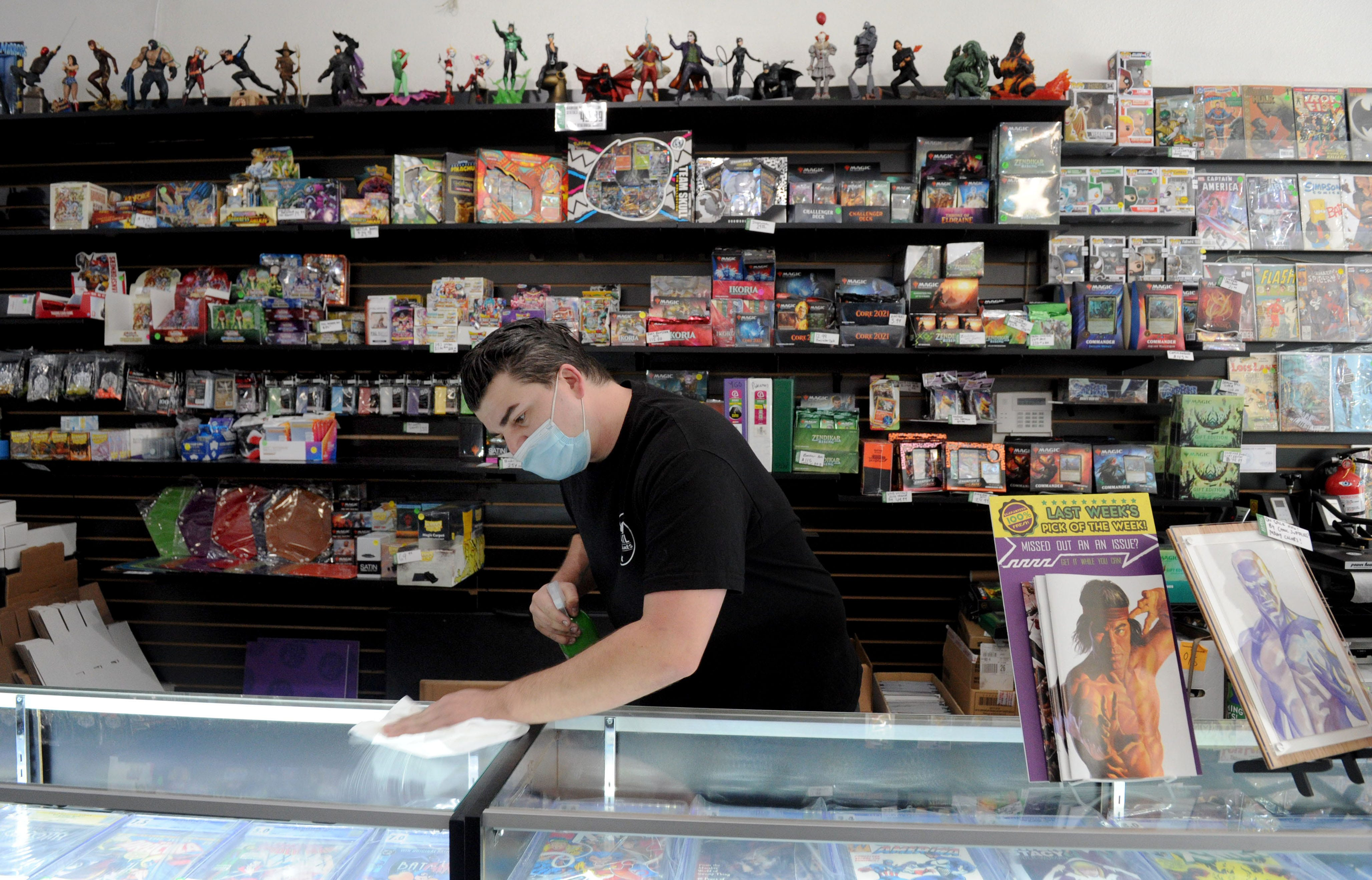 Timmy Heague, owner of Arsenal Comics & Games, sanitizes a display case at his store in Ventura on Thursday, Nov. 19, 2020. As a small business owner, Heague has had to adapt the way he does business to ensure it can stay open.