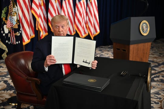 President Donald Trump signs executive orders on Aug. 8, 2020 in Bedminster, New Jersey. 2020.