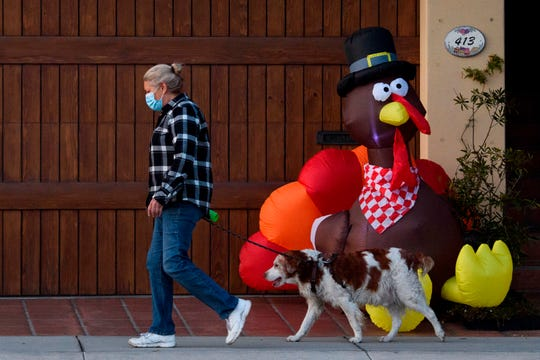A pedestrian wearing a face mask walks their dog past an inflatable turkey ahead of the Thanksgiving holiday during increased Covid-19 restrictions in Manhattan Beach, California, November 21, 2020.