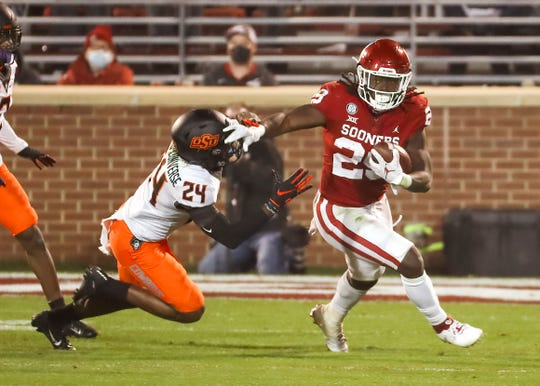 Oklahoma running back Rhamondre Stevenson (29) stiff-arms Oklahoma State cornerback Jarrick Bernard-Converse during the first half at Gaylord Family-Oklahoma Memorial Stadium.