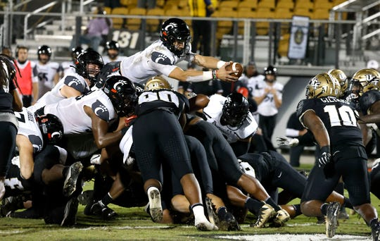 Cincinnati quarterback Desmond Ridder (9) dives over the top for a touchdown during the second half against Central Florida at the Bounce House in Orlando.