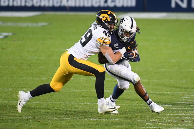 Iowa linebacker Nick Niemann tackles Penn State running back Caziah Holmes during the second quarter at Beaver Stadium.
