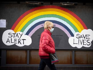"A pedestrian wearing a face mask or covering due to the COVID-19 pandemic, walks past COVID-19 street art, advising to ""Stay Alert"" anfd ""Save Lives"" in central London, on Nov. 22, 2020."