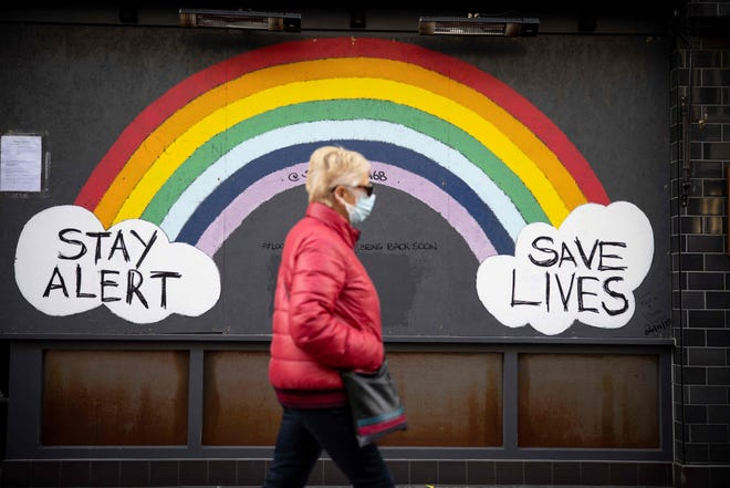 """A pedestrian wearing a face mask or covering due to the COVID-19 pandemic, walks past COVID-19 street art, advising to """"Stay Alert"""" anfd """"Save Lives"""" in central London, on Nov. 22, 2020."""