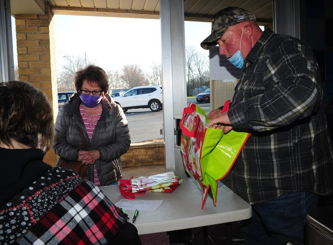 Steve Frederick prepares an order for Joyce Kowalczyk, center, Nov. 14 duringSt. Ann Church's annual pierogi sale. The sale was postponed from Lent earlier this year due to the pandemic.