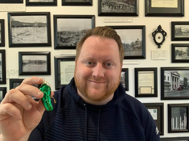 Cleo Redd Fisher Museum Curator Kenny Libben holds a glass pickle ornament. The museum will hide a glass pickle ornament, each day, somewhere in the Mohican area as part of a community scavenger hunt with prizes.
