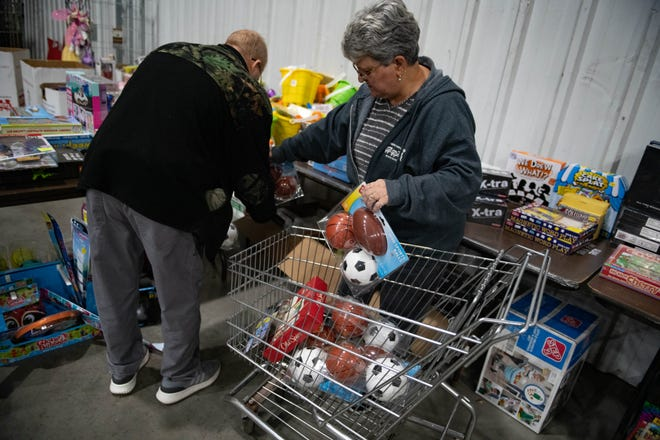 Frank Moffatt, left, and wife Pat, of Conway, organize Toys for Tots toys Monday afternoon in a warehouse in Leetsdale.