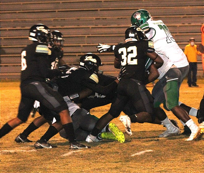 The defensive trio of Derek Beebe (6), Frank Ford, Jr. (5) and Christian Patterson (32) combine on the tackle during Leesville's win Friday night over Peabody, 42-12.
