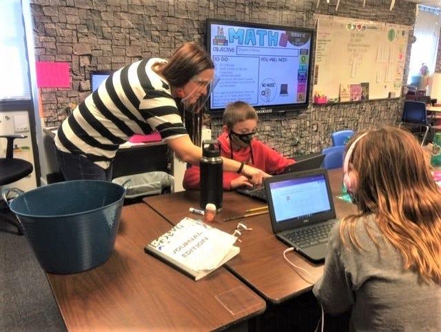 Fifth-grade teacher Carrie Christensen helps students do their work at Wilson Elementary School.