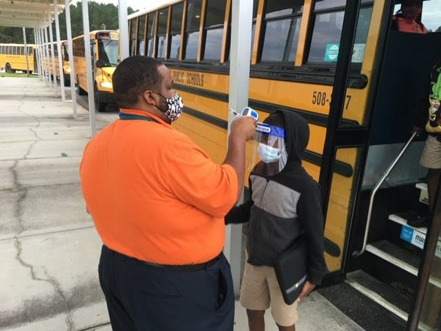 A staff member on the Jasper County School District's Hardeeville campus checks students' temperatures as they leave the bus.