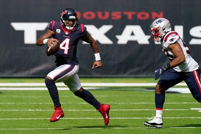 Houston Texans quarterback Deshaun Watson runs past New England Patriots linebacker Josh Uche in the first half on Sunday.