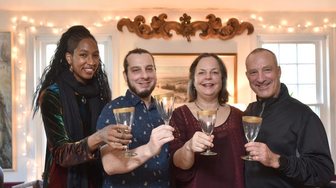 Lauren Wolk, third from left, and her husband, Richard Hall, with son Ryland Hall and his girlfriend, Athena-Gwendolyn Baptiste, raise family heirloom glasses in a holiday toast. The four, and perhaps Wolk's mother, will be the only ones at their Thanksgiving table this year because of the pandemic.