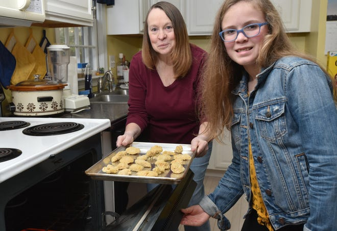"Riley Coleman, 9, front, and her grandmother Holly Seaver of Marstons Mills teamed up to create a cookbook, ""Riley's Family Cookbook,"" and the proceeds will go to helping families in Haiti and in two churches here in the United States.   [Steve Heaslip/Cape Cod Times]"