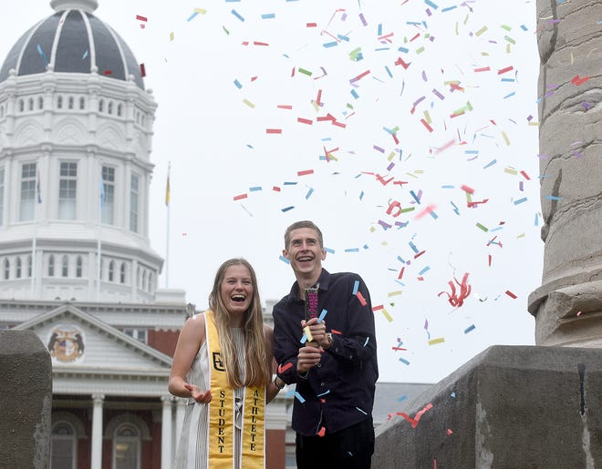 Zoe Cross, a graduating senior soccer player at the University of Missouri from London, England, poses for graduation photos with her boyfriend Kieran Wood, a senior track team member from Cambridge, England, who will graduate next May at MU, on Monday near the columns at the Francis Quadrangle during a light rain. The December graduation ceremony will be held online because of the COVID-19 pandemic.