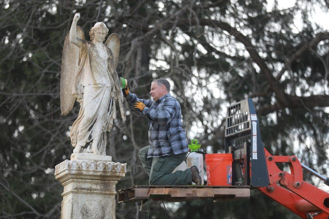 Randy Rogers cleans the angel statue atop the monument for Revolutionary War soldier William Walcutt.