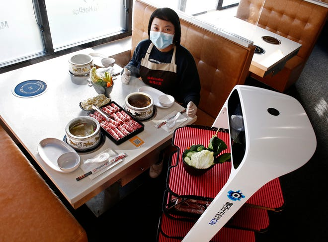 Mala HotPot manager Yvonne Cao demonstrates how customers receive food from a robot at the Hilliard restaurant.
