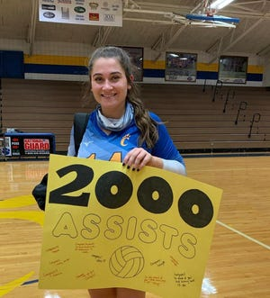 Southwestern Randolph volleyball player Peyton LeRoy holds a sign celebrating 2,000 career assists. [Contributed photo]