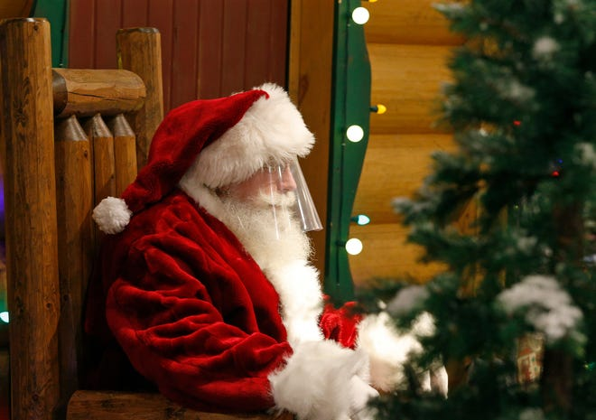 Santa Claus sits behind a plexiglass barrier at Bass Pro Shops in Daytona Beach, Saturday, Nov. 21, 2020. The beloved man in the velvety red suit is making multiple visits throughout Volusia County this month leading up to Christmas.