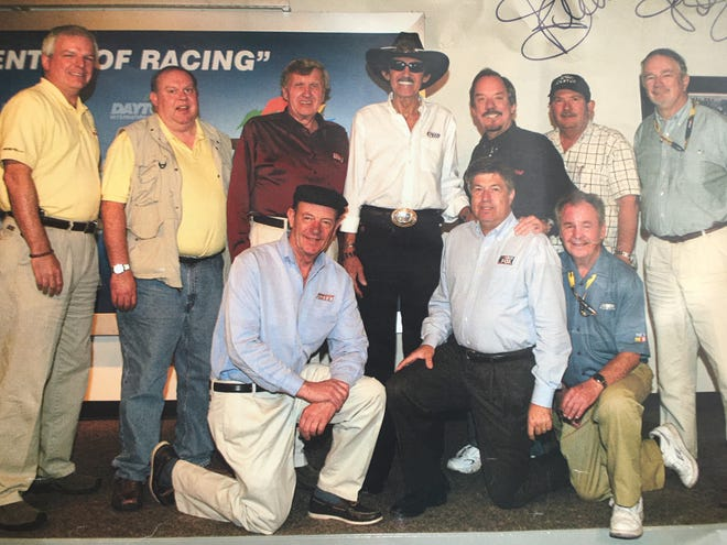 Godwin Kelly (top row, second from right) with a bunch of colleagues at Daytona more than 10 years ago. Front row from left: Dick Berggren, Mike Joy, the late Barney Hall; top from left: Mike Hembree, Ed Hinton, Ken Squier, Richard Petty, Steve Waid, Godwin, and Al Pearce.