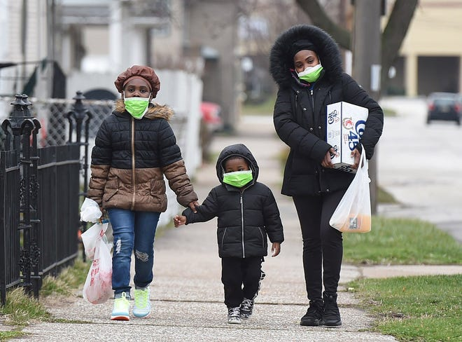 A mother and her two children wear their masks as they return home from shopping in Erie, Pennsylvania.
