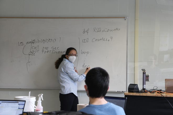 With plastic shields at lecterns, student desks at 6-foot intervals, and all students wearing masks, Alfred State found no incidents of COVID-19 spread by attendance at in-person lectures this fall. Pictured is Dr. Maryam Nasri, an assistant professor in the Mechanical and Electrical Engineering Technology Department.