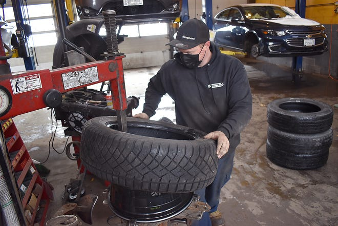 James Poindexter, a technician with Tallmadge Tire of Cortland, mounts tires Wednesday at the shop. Beyond the first snow of the season, temperatures have dropped enough so snow tires won't wear unduly, which can happen when the road is warmer than 45 or 50 degrees.