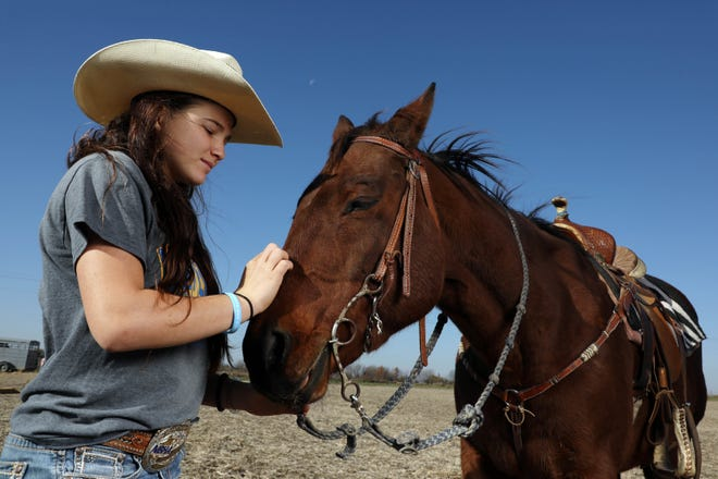Barrel racer Madi Lundvall, 16, photographed with her horse Jewel, following a practice session in the family arena, Saturday Nov. 7, 2020 South of Wapello. Madi will be traveling to Guthrie, Oklahoma in January to compete at the International Miniature Rodeo Association finals in barrel racing. Her brother Cade, 13, a bull rider will also compete in the finals.