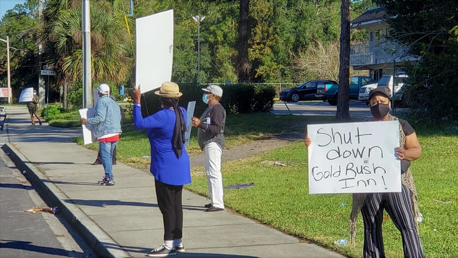 About 20 people lines Harts Road Monday with signs demanding more police response and to shut down the Gold Rush Inn behind this group, and the River City Inn nearby due to crime problems.