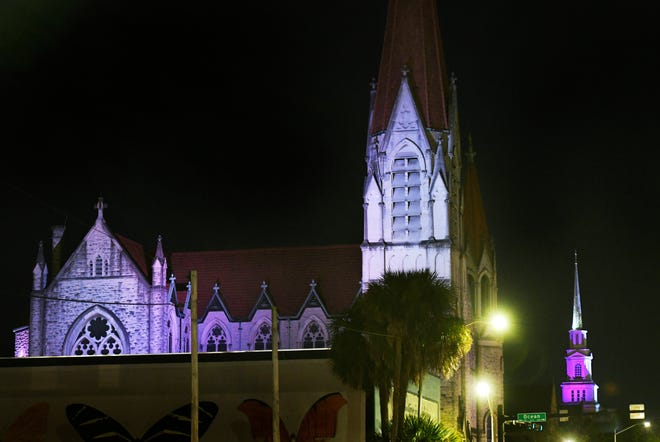 Colored spotlights on the Basilica of the Immaculate Conception and the First United Methodist Church steeple (background) are part of the Christmas in the Cathedral District 2020: Let There Be Light display.