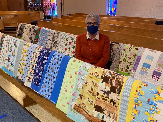 CAMBRIDGE - Deb Dobbels sits amongst the 61 quilts and blankets that the ladies from the St. John Vianney Catholic Church's Altar & Rosary Society completed.  They will be delivered to the Neonatal Unit at the Children's Hospital of Peoria.