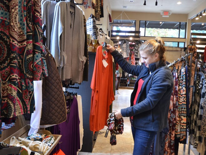 Betty Clark looks at jewelry inside Under the Eiffel Boutique in Downtown Denison during Small Business Saturday in 2016.