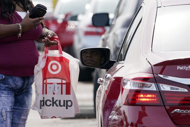 A Target employee prepares to hand a customer a curbside pickup purchase in Jackson, Miss., Thursday, Nov. 5, 2020.  Retailers and carriers are preparing for a holiday shipping  surge that could mean delays in holiday gifts. Stores are pushing their customers to buy early to smooth out the peaks in the weeks leading up to Christmas. And they're further expanding services like curbside pickup to minimize online shipping.   (AP Photo/Rogelio V. Solis)