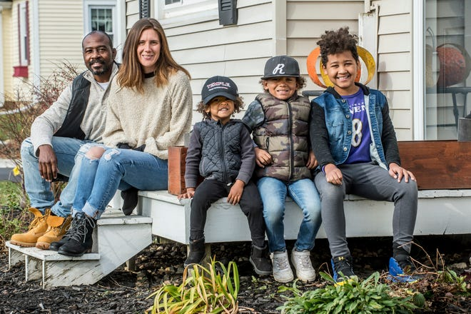 T.J. and Chelsea Williams sit with their chilldren, from left, Quinnton, 3, Myles, 6, and Aidan, 10, in front of their Washington home on November 23, 2020. T.J., a Tremont wrestling coach, is recovering from a chest tumor.