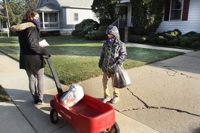Jennifer Hess, left, pulls the red wagon as her son Hunter places donated food in it to be given to the Salvation Army on Saturday in Freeport. The mother/son duo have been placing flyers in their neighborhood to enlist donations.