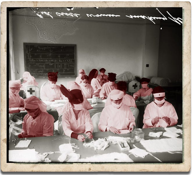 Red Cross woen sit at long tables making influenza masks in Chicago in 1928.